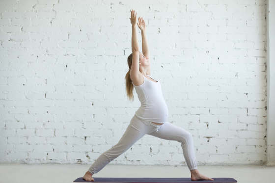 Pregnancy Yoga and Fitness concept. Portrait of beautiful young pregnant yoga model working out indoor. Pregnant happy fitness person enjoying yoga practice at home. Prenatal Warrior I posture